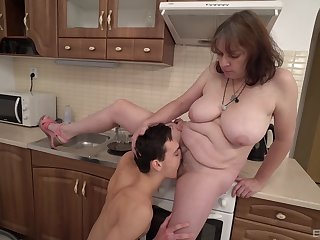 Dirty mature mommy drops chiefly her knees to suck a younger dude's cock